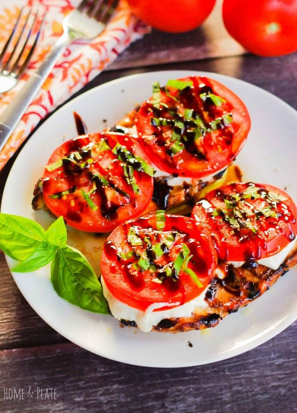 Grilled chicken topped with cheese tomato slices balsamic reduction and basil