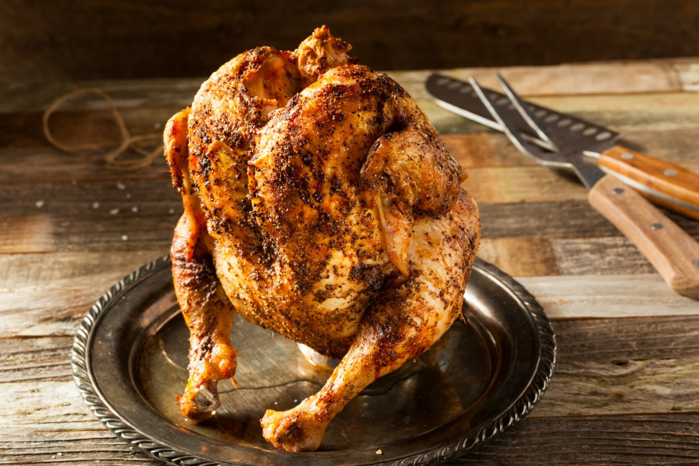 BBQ whole Chicken on a silver plate standing on a beer can