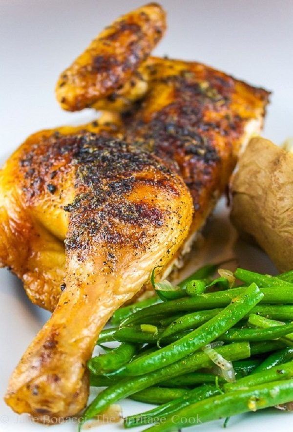 Quarter Chicken on a white plate with green beans and baked potato