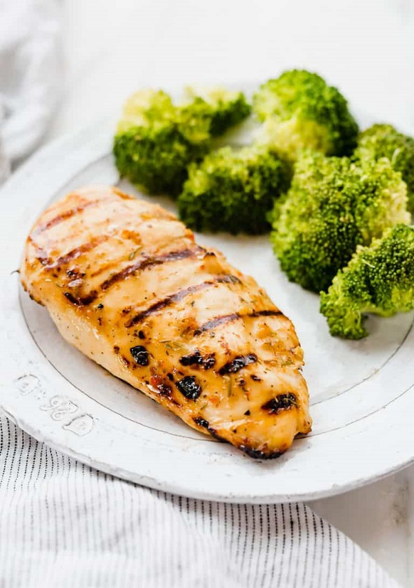 Grilled Chicken breast on a white plate with broccoli