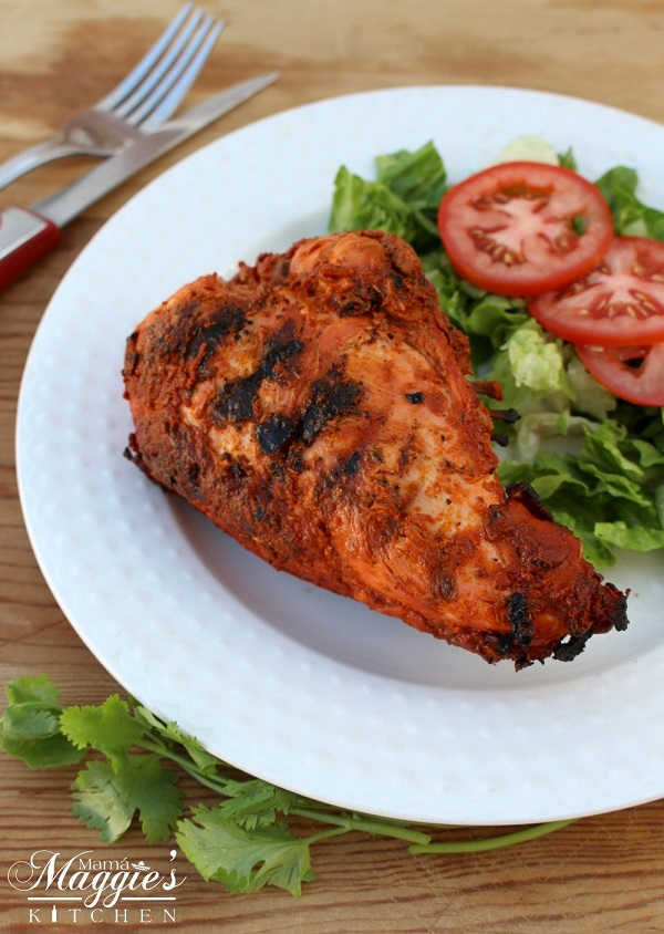 Grilled chicken breast on a white plate with green salad and tomato slices