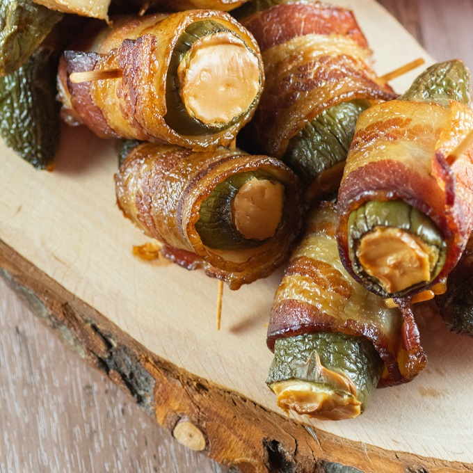 Jalapeno poppers stacked on a wooden serving board