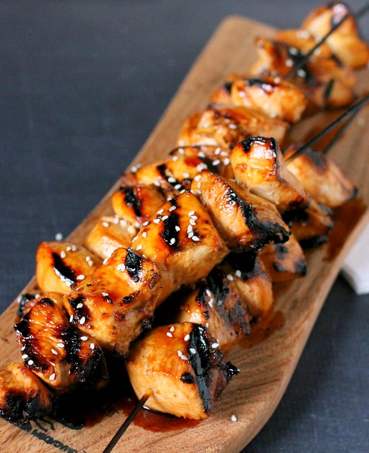 Grilled Chicken cubes on a skewer laying on a wooded board
