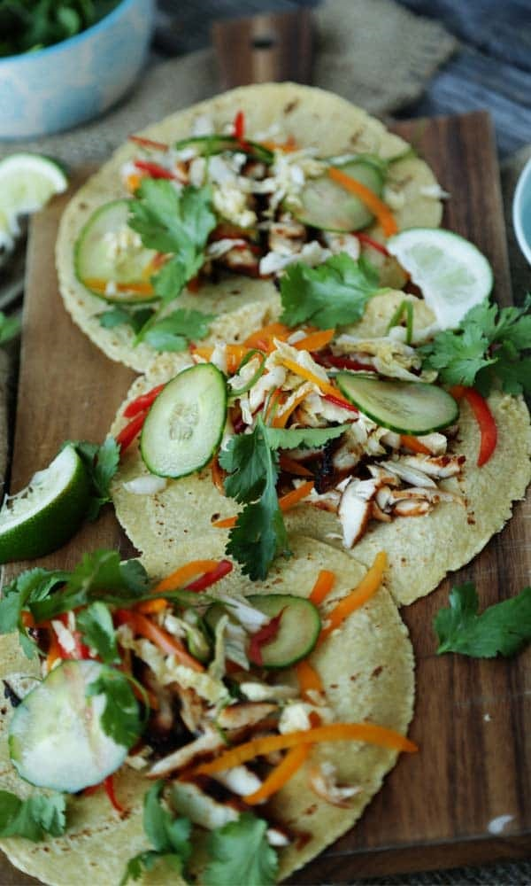 Chicken tacos with cucumber slices carrot strips and cilantro with lime wedges on a wooden board