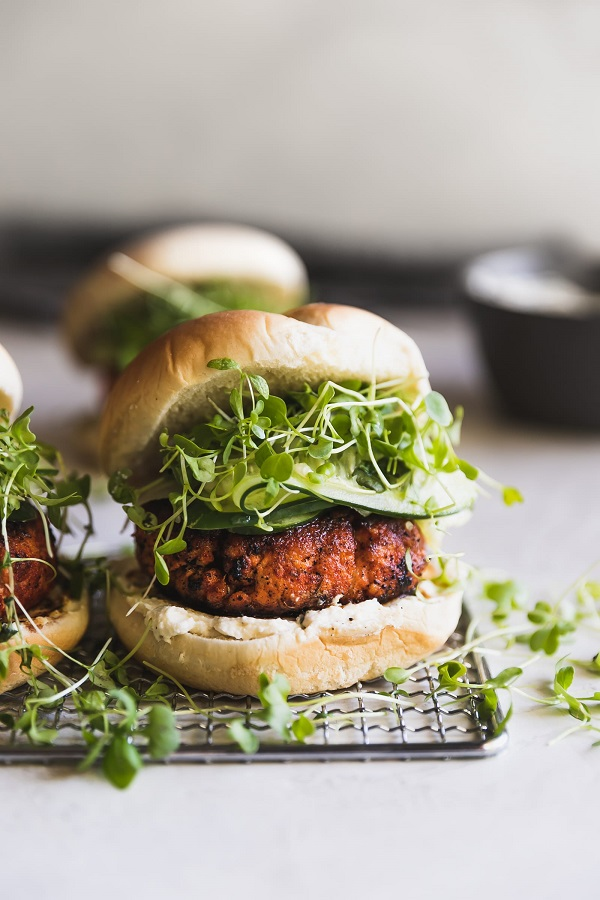 Blackened salmon burger with green sprouts on a cooling rack