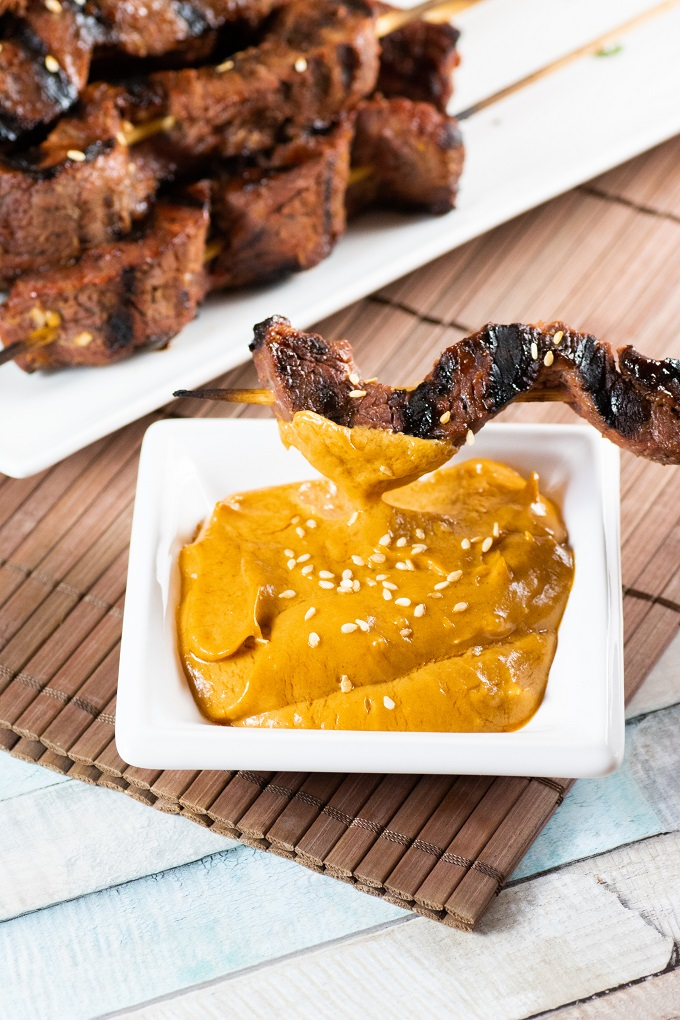 Beef Satay Skewer in peanut dipping sauce on a brown place mat