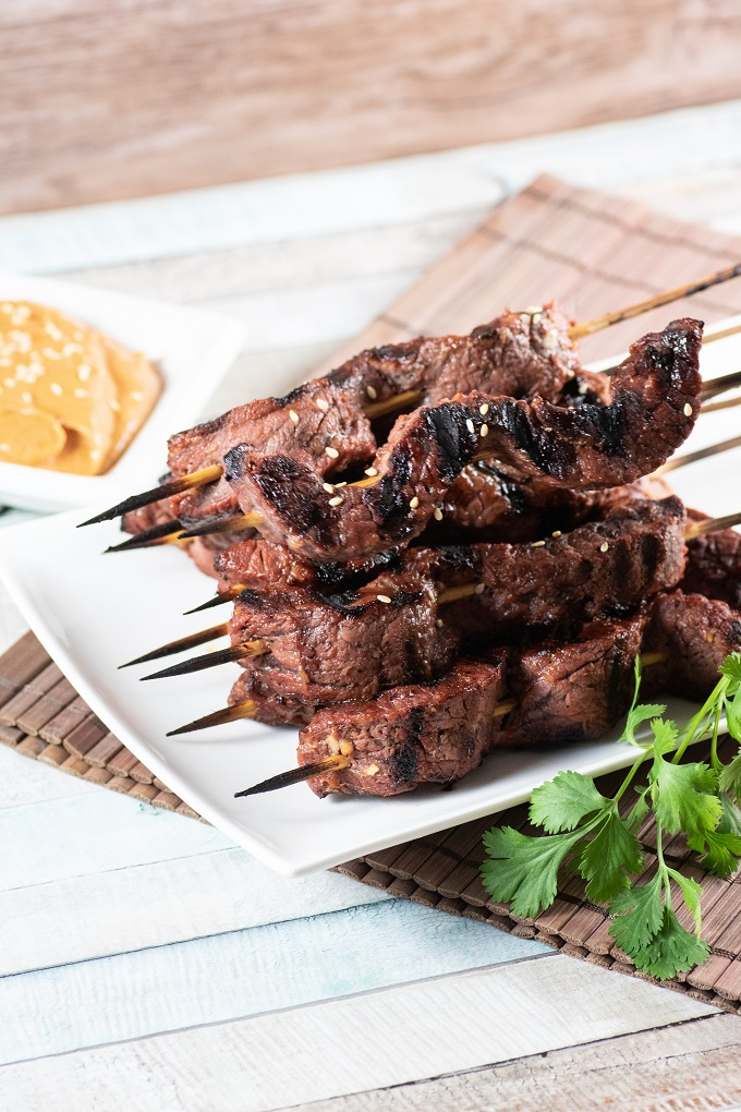Beef Satay skewers stacked on a white with parsley