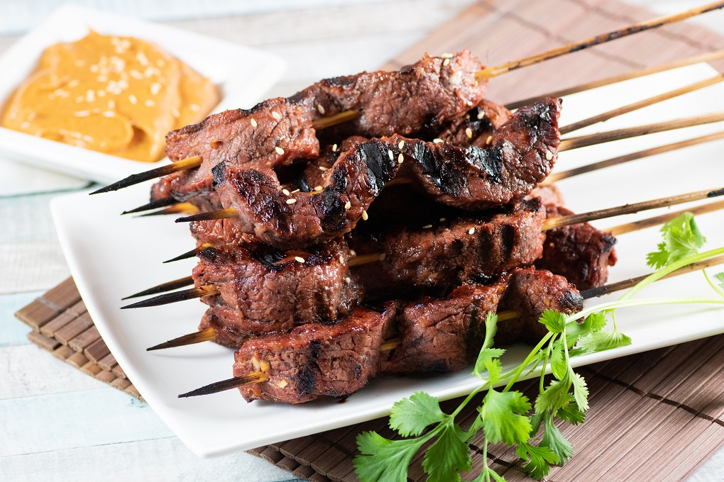 Grilled beef satay skewers on a white plate with peanut dipping sauce and parsley