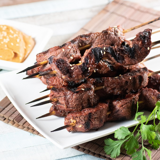 Beef satay skewers stacked on a white plate with peanut dipping sauce