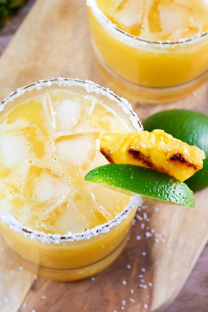 Grilled pineapple margarita on a board garnished with lime and grilled pineapple