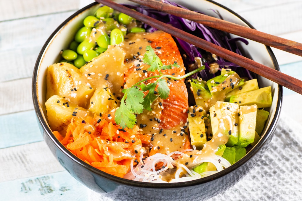 Grilled salmon in a black bowl with fresh veggies on a bed of vermicelli