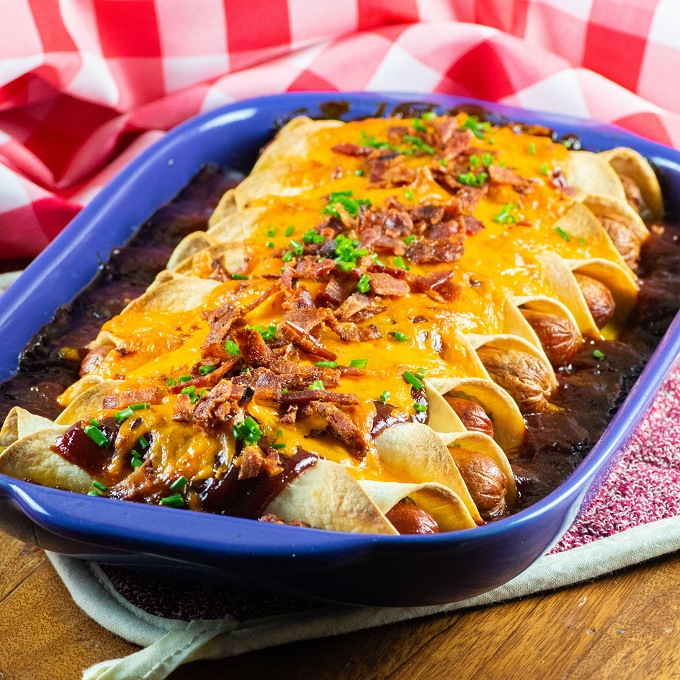 Grilled tortilla wrapped hot dogs in a blue casserole dish covered with melted cheese and bacon