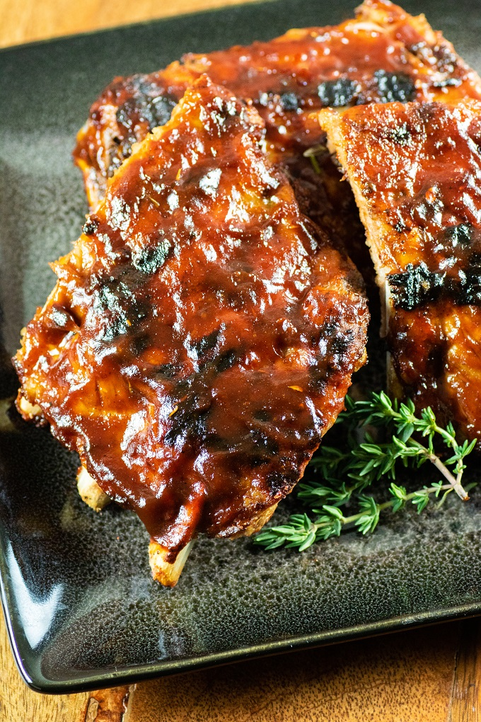 Grilled Baby Back Ribs covered with BBQ Sauce on a black plate with a sprig of thyme