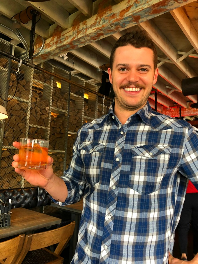 Picture of Ben Fellows GM of the Comery Block Restaurant holding an Old Fashion drink