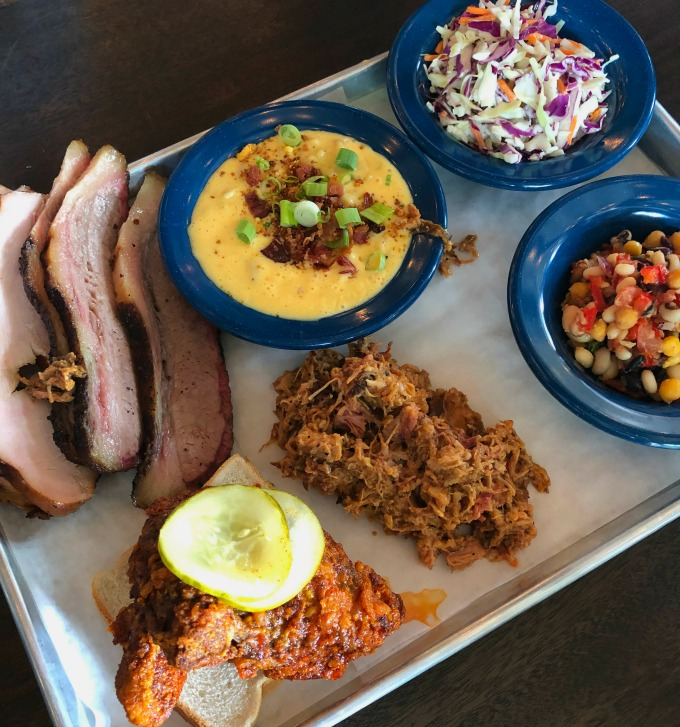 Tray of smoked meats, mac and cheese, coleslaw and bean salad