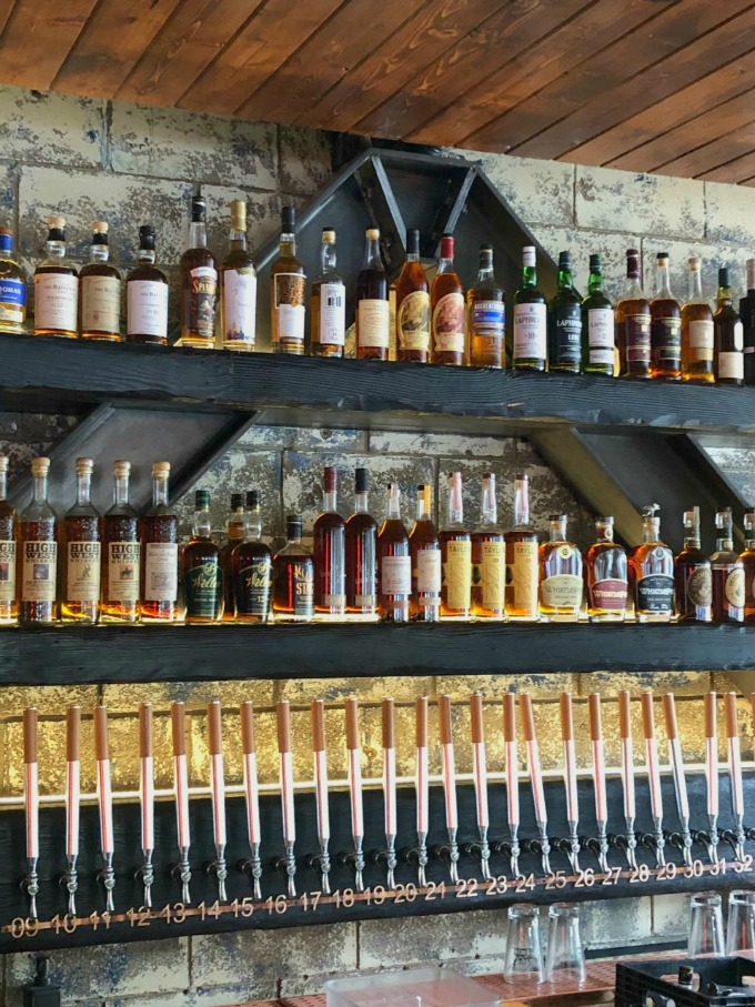 Whiskey bottles and beer taps behind the bar in the Comery Block Restaurant