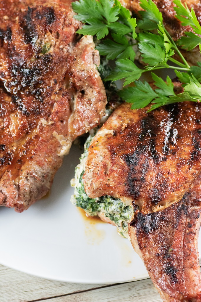 Cooked grilled stuffed pork chops on a white plate with parsley