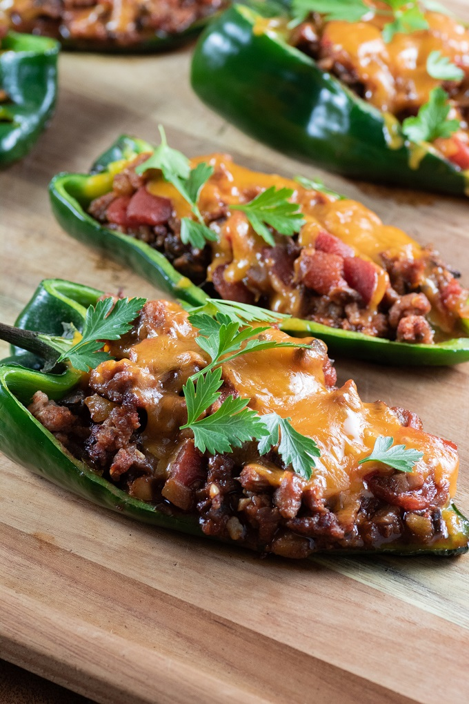 Stuffed poblano peppers on a wooden board with melted cheese and parsley
