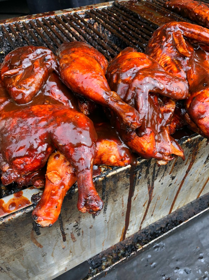 Smoked chicken quartered and covered with BBQ sauce on the grill