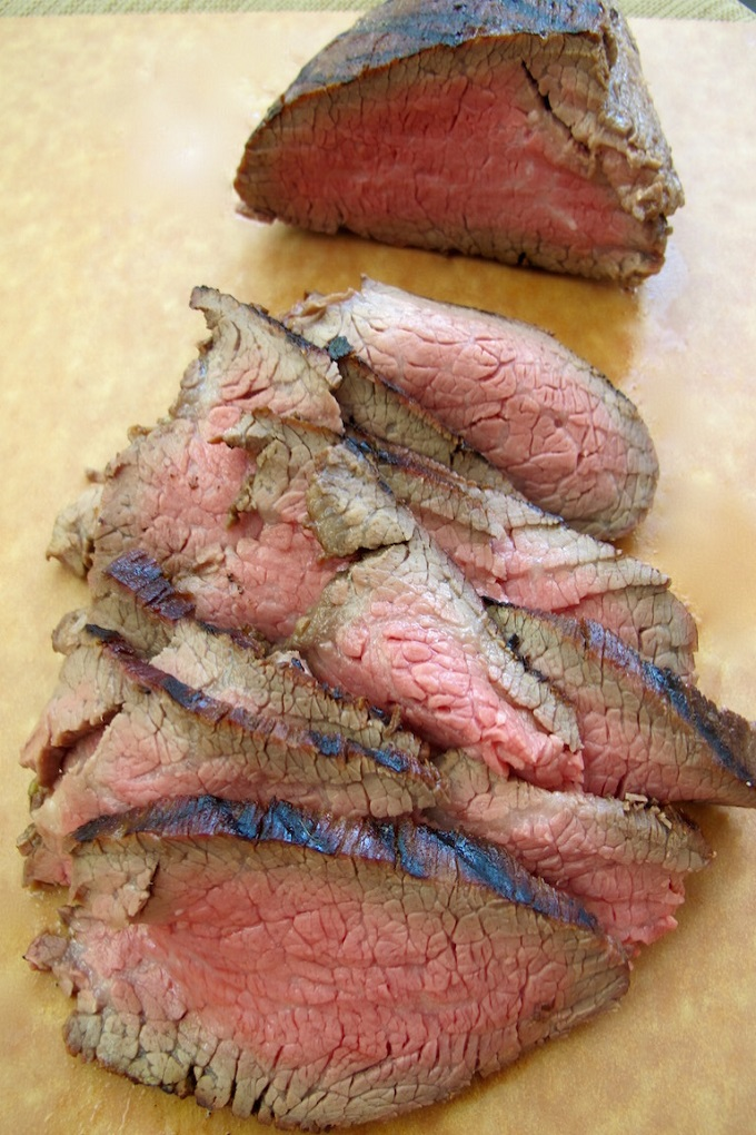 Slices of grilled tri tip steak on a wooden cutting board