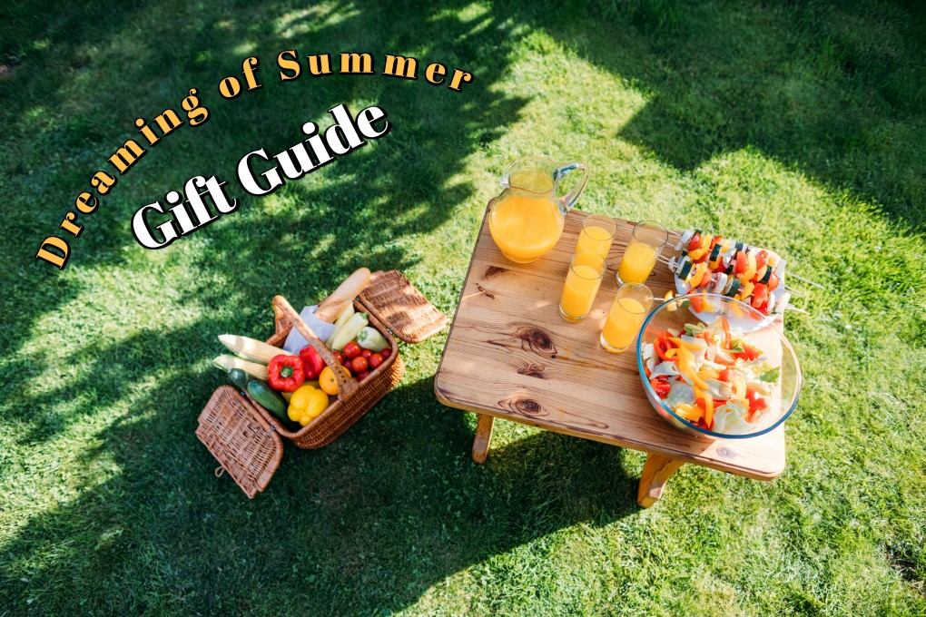 Picnic basket full of vegetables beside a wooden picnic table with orange juice and fruit on it
