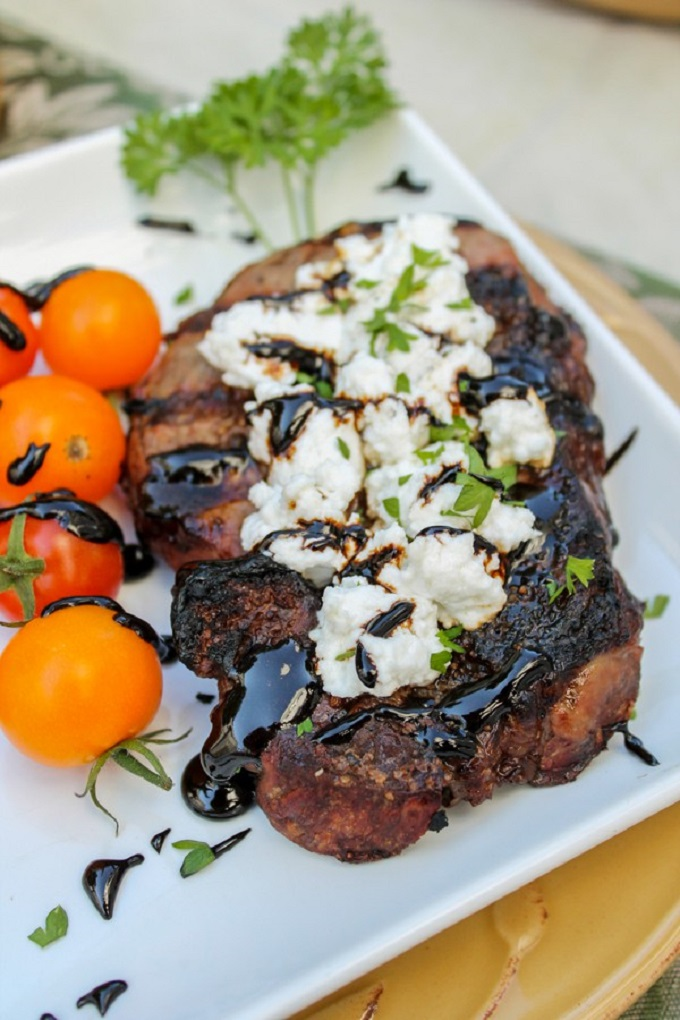 Steak topped with goat cheese and balsamic reduction on a white plate with orange tomatoes
