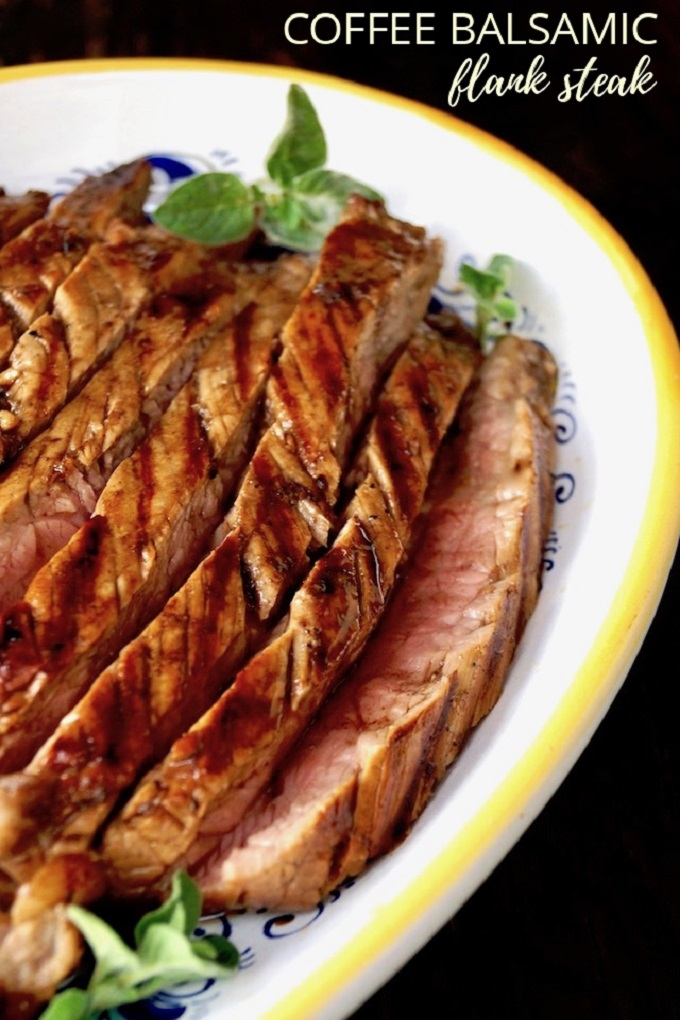 Sliced flank steak in a coffee balsamic sauce on a white and yellow plate