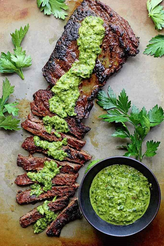 Skirt steak sliced in a board with chimichurri sauce on top