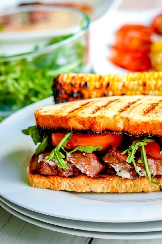 Steak Sandwich on a white plate with tomates and toasted bread