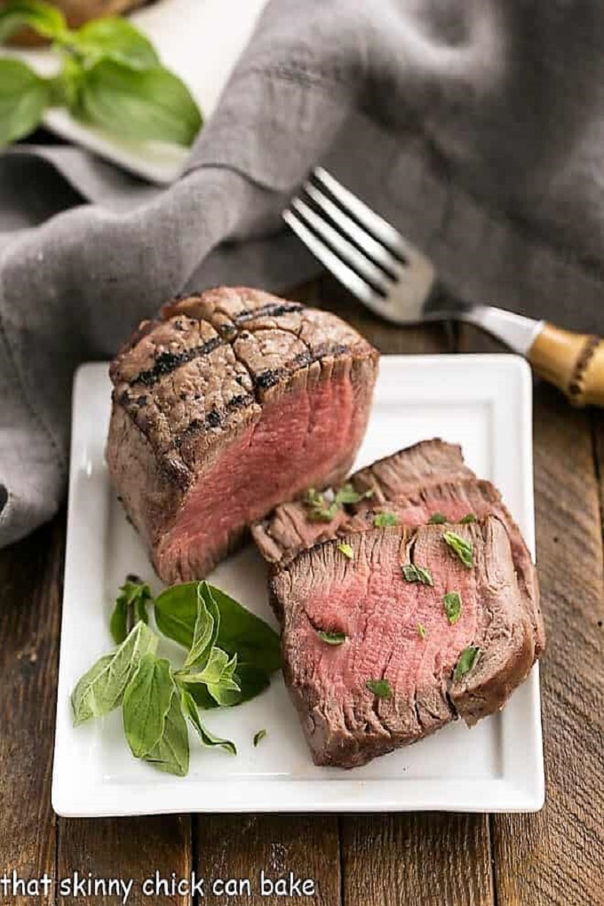 Grilled tenderloin with garlic herb butter on a white plate with a fork