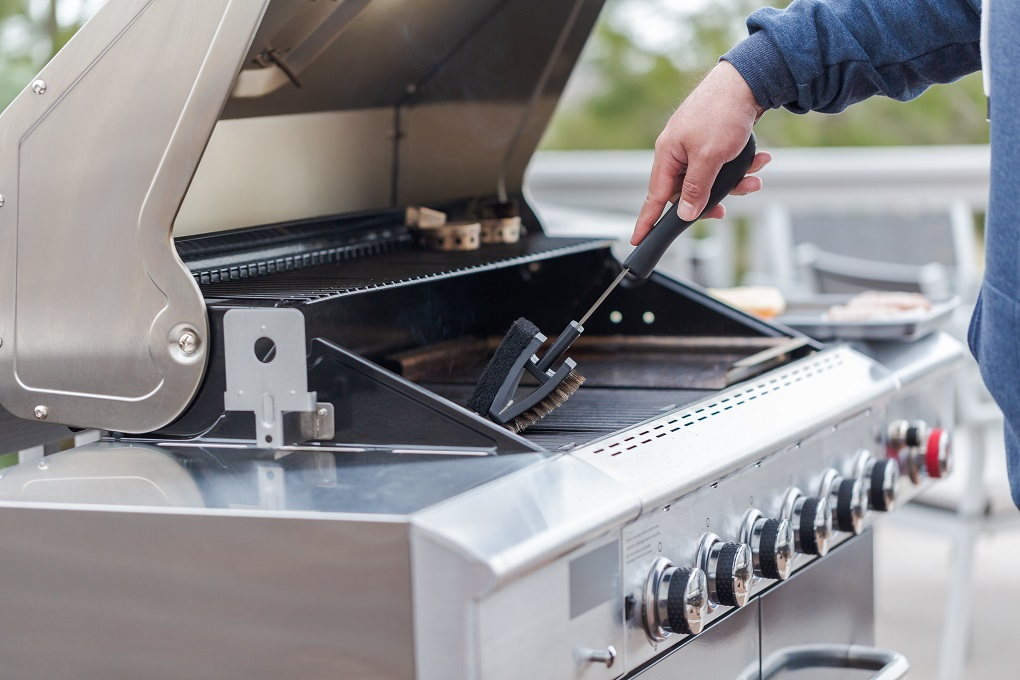 Stainless Steel BBQ Grill being cleaned with a wire brush