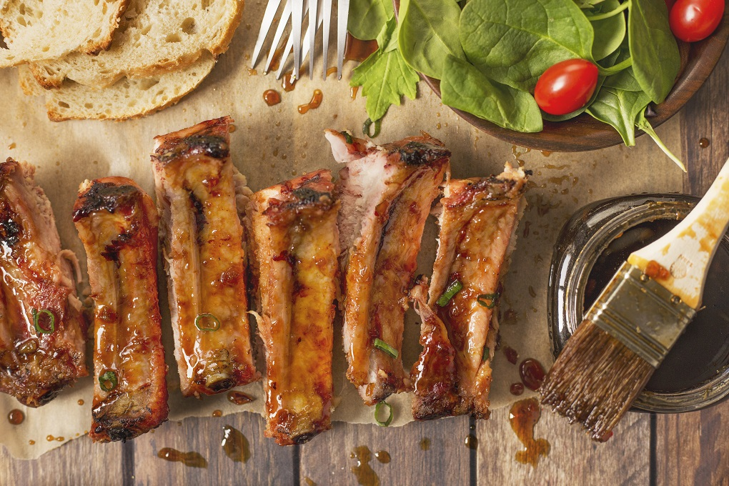 individual Pork Ribs covered in jack Daniels sauce on butcher paper with a brush and jar, salad and bread slices