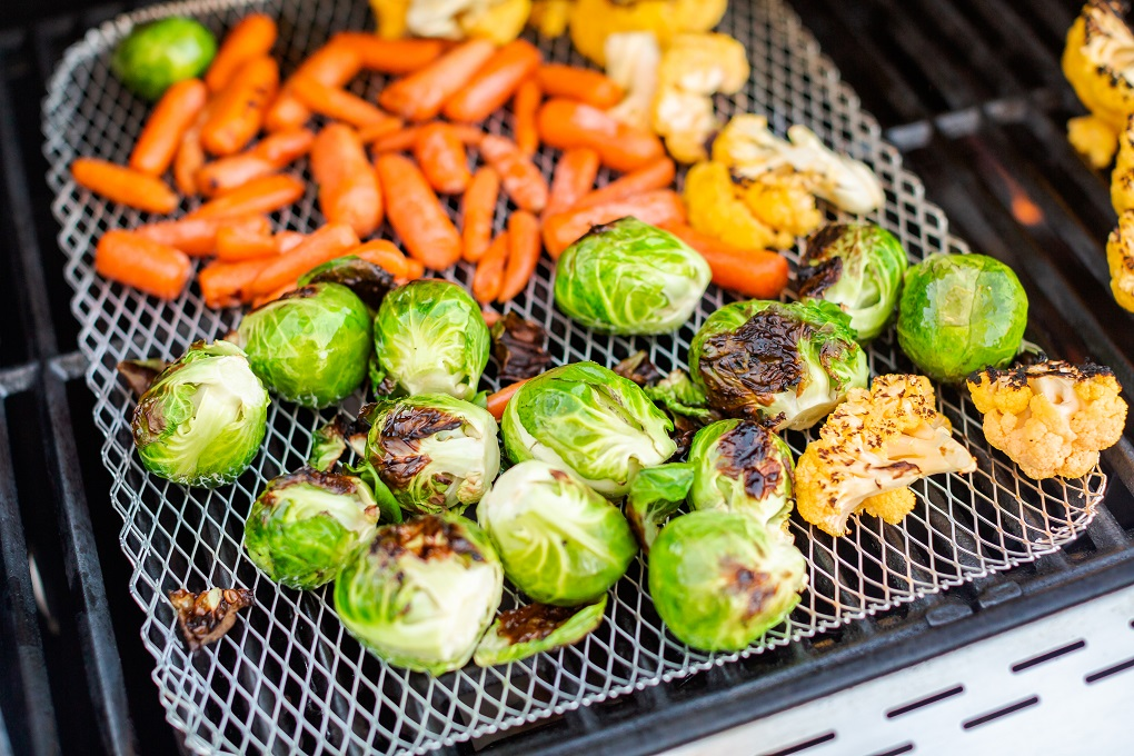Brussels sprouts and other veggies on a grill pan on the BBQ