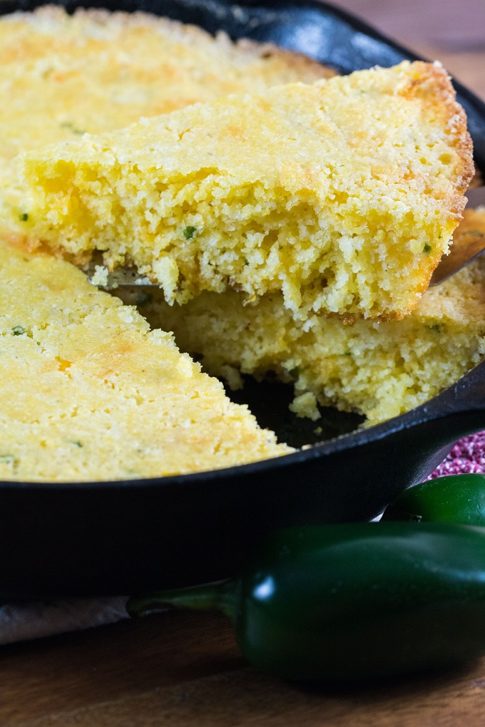 A slice of cornbread taken out of the cast iron skillet with jalapeno peppers around the pan