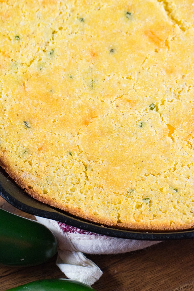 The edge of the cooked corn bread in a cast itron skillet