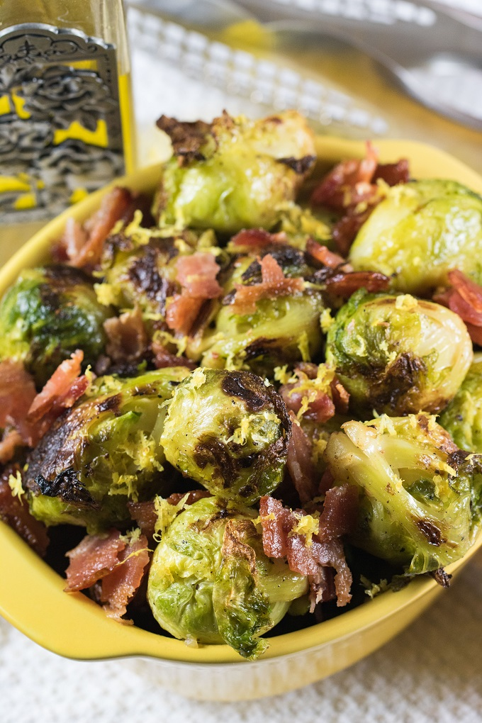 Grilled Brussels sprouts with crispy crumbled bacon in a yellow bowl