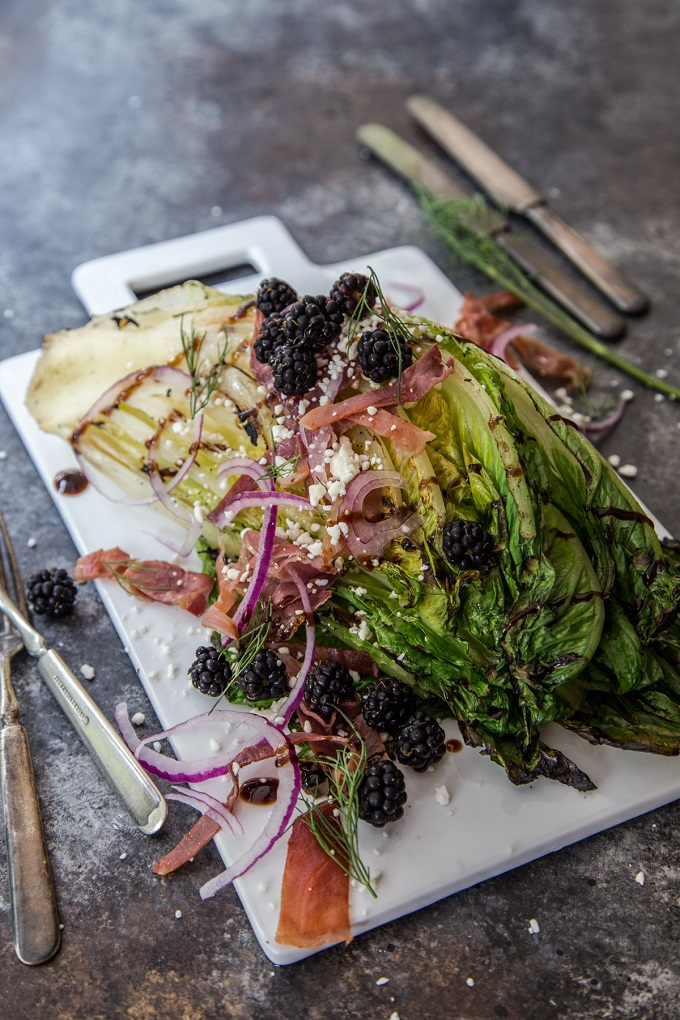 Grilled romaine lettuce with blackberries in a white board