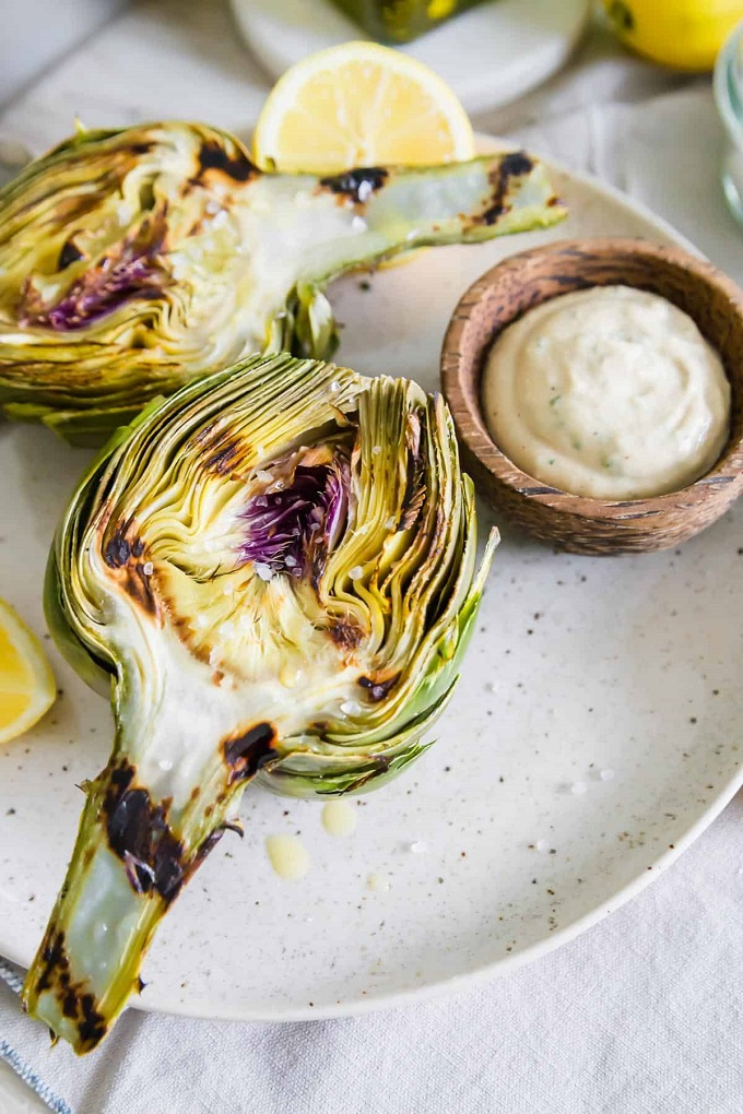 Grilled artichokes halves on a white plate with lemon slices