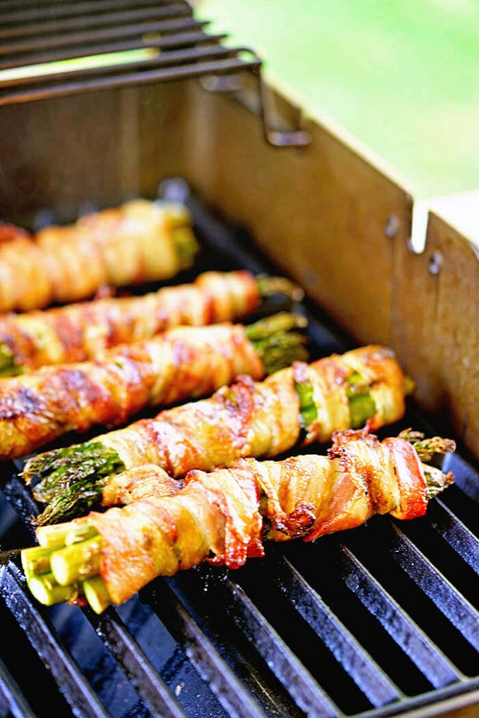 bacon wrapped asparagus cooking on the grill