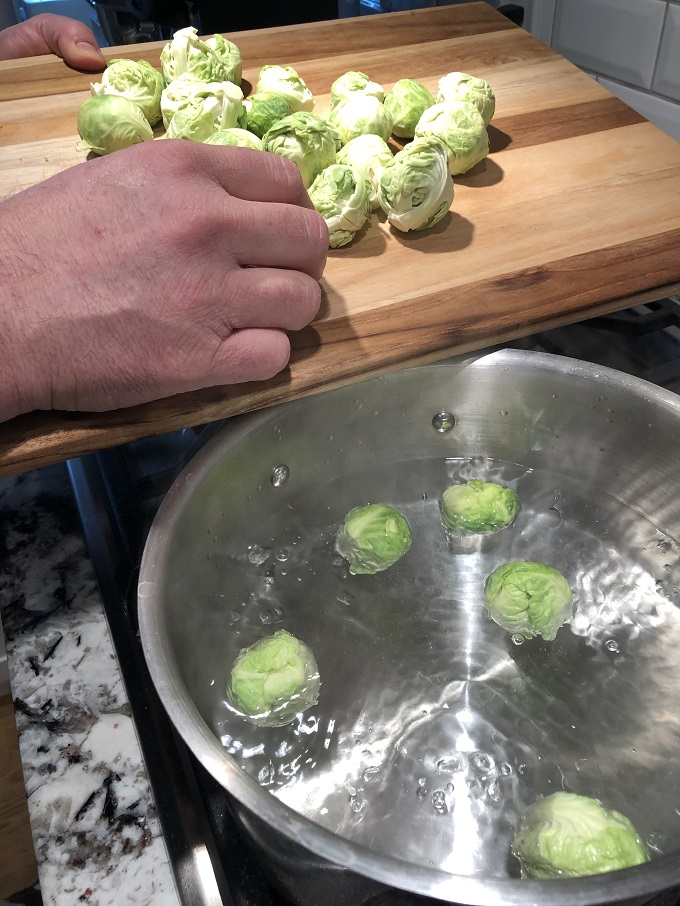 Putting Brussels sprouts into boiling water.