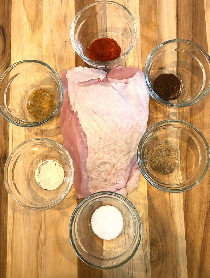 Raw turkey breast with all the spices in glass bowls on a wooden cutting board
