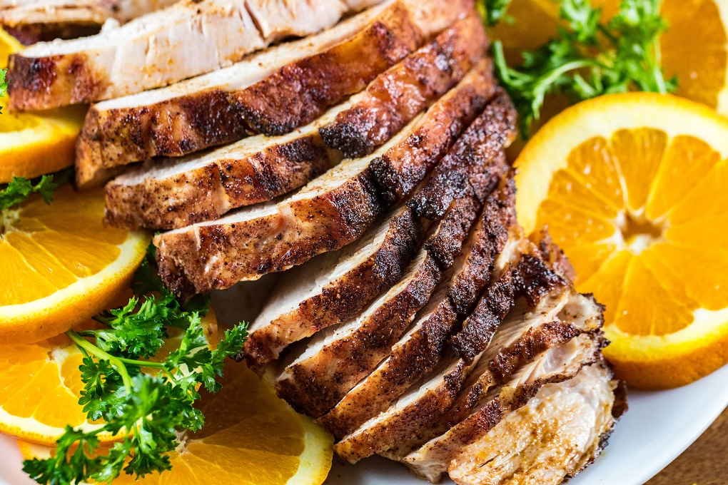Close up of southwest grilled turkey breast slices with ornage slice sand parsley on a white plate