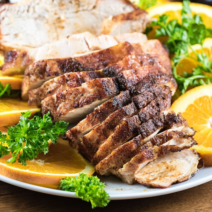 Southwest grilled turkey breast sliced on a white plate with orange slices and parsley