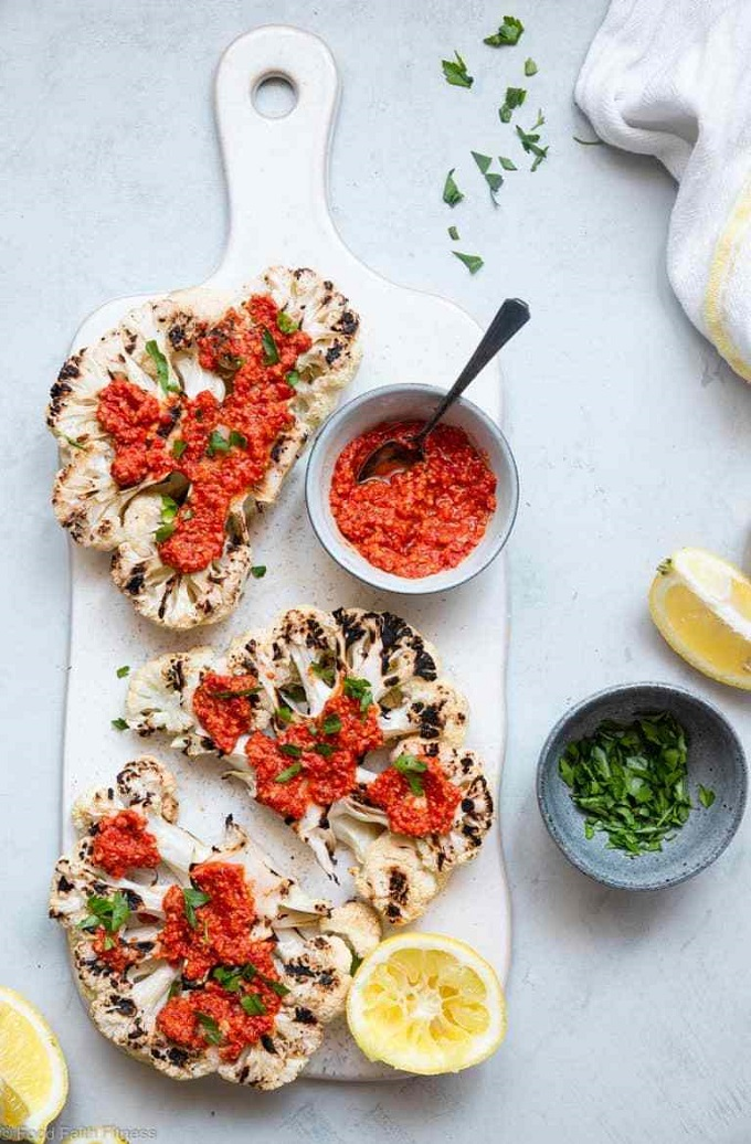 Grilled cauliflower steaks with Romesco sauce on a white board