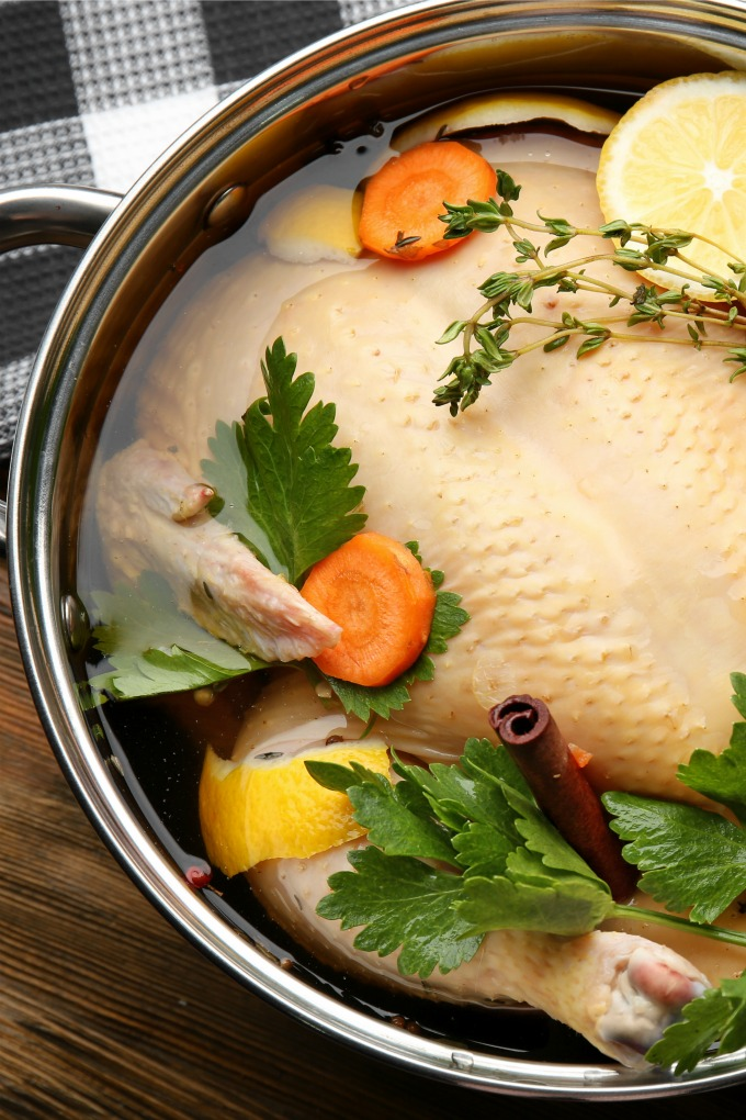 Turkey brining in a large pot with herbs and vegetables