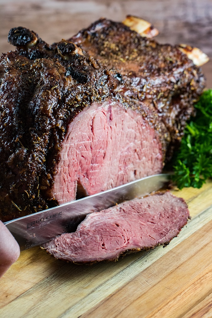 Prime Rib with one slice off on a wooden cutting board