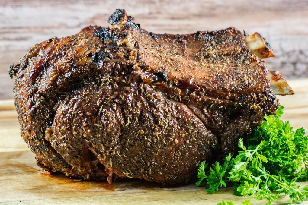 Perfectly grilled prime rib roast on a wooden cutting board with parsley