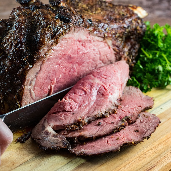 Slicing prime rib roast on a wooden cutting board