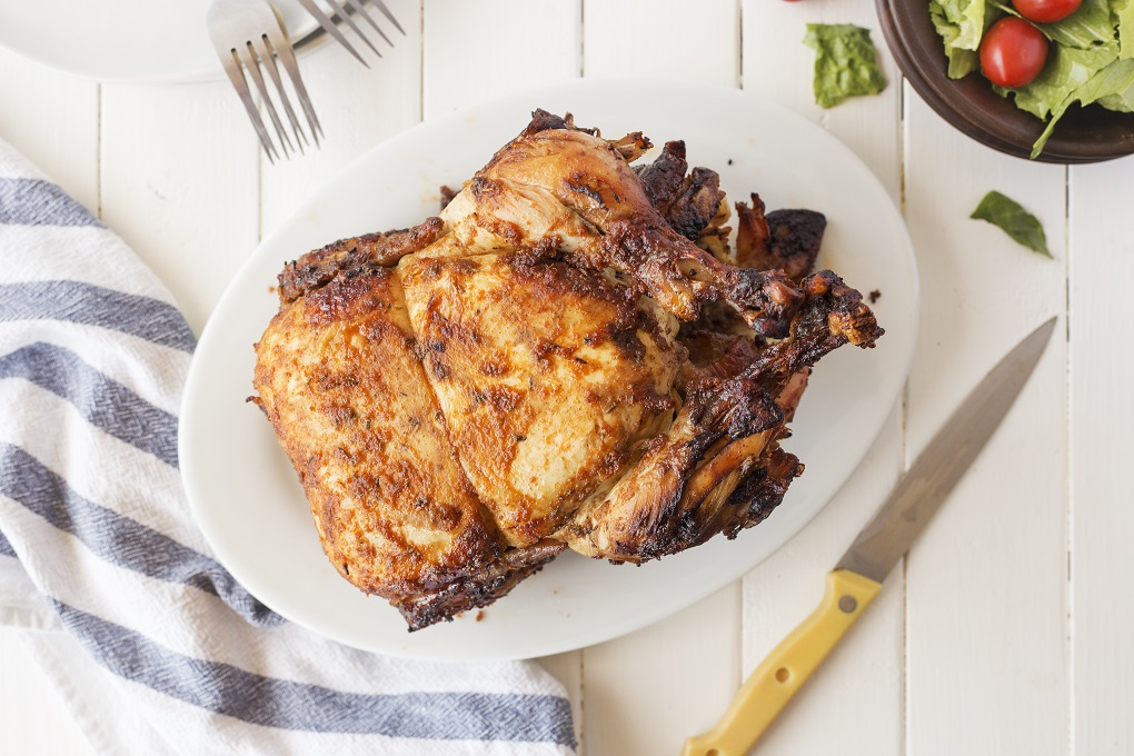 Whole cooked rotisserie chicken on a white plate with forks a knife and a green salad