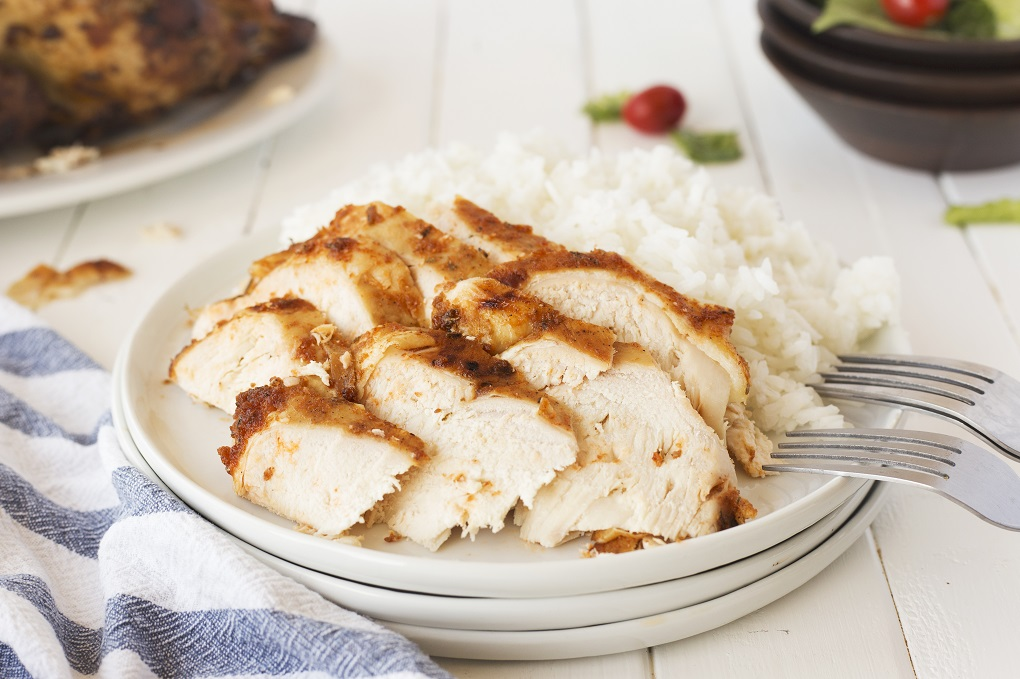 slices of rotisserie chickern on a white plate with rice and 2 forks